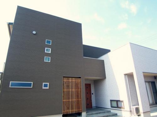 青空に生える重厚感あふれる二世帯住宅の家